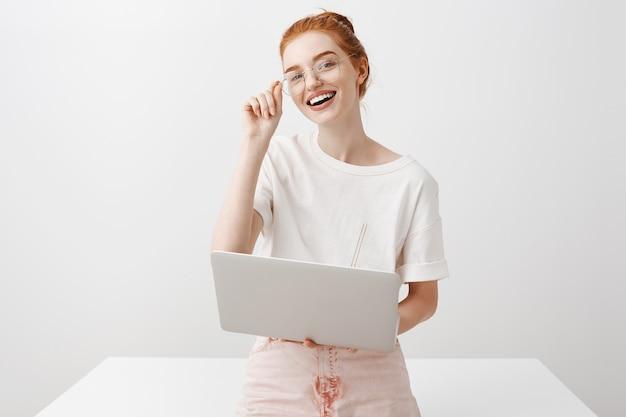 Улыбающаяся рыжая девушка с помощью ноутбука и глядя