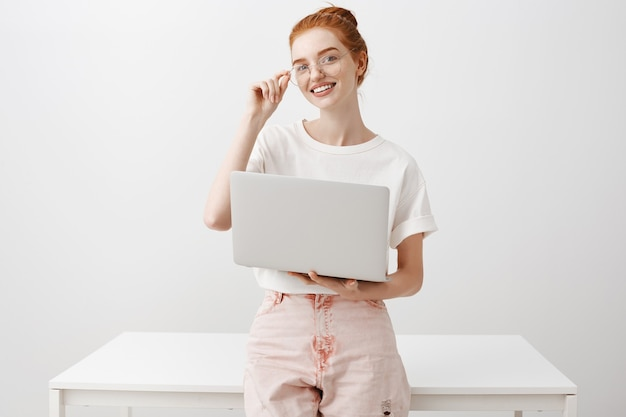 Smiling redhead girl using laptop and looking