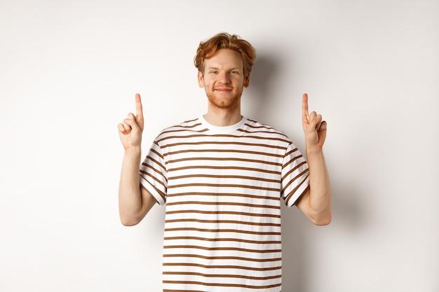 ひげを生やした赤毛の男に笑みを浮かべて、指を上に向けて広告を表示し、白い背景の上に立って