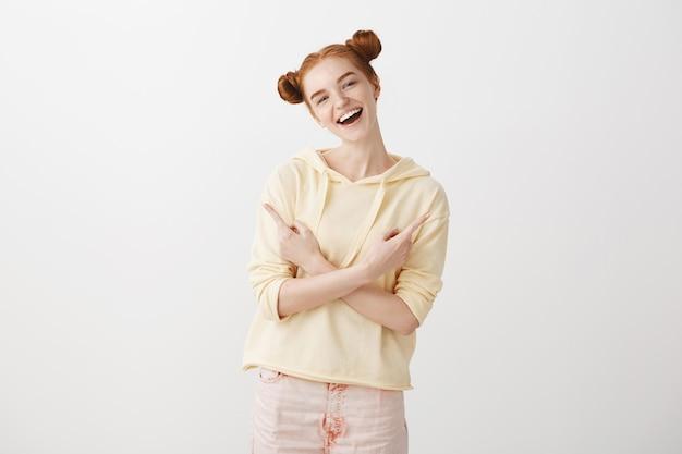 横向きの指を指す笑顔の赤毛のうれしそうな女の子