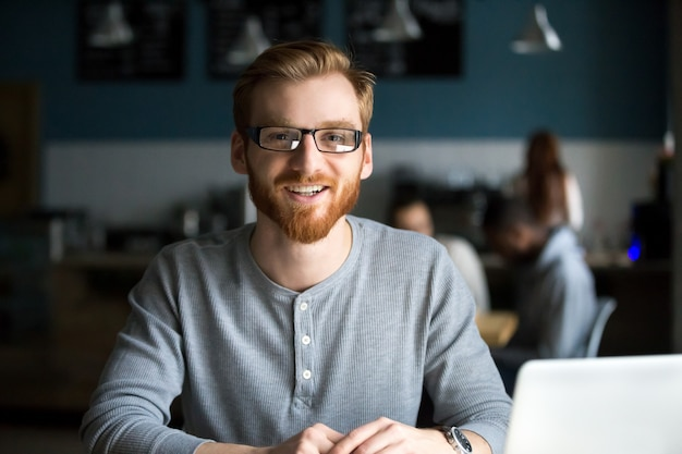 Smiling redhead man with laptop looking at camera in cafe