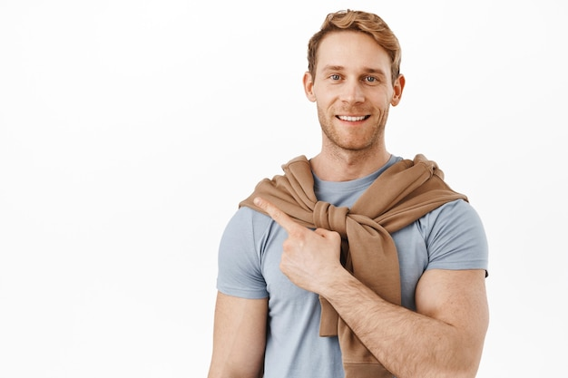 筋肉の大きな上腕二頭筋と笑顔の赤毛の男、左上隅を指して、コピースペースに製品の広告を表示し、白い壁の上に立って