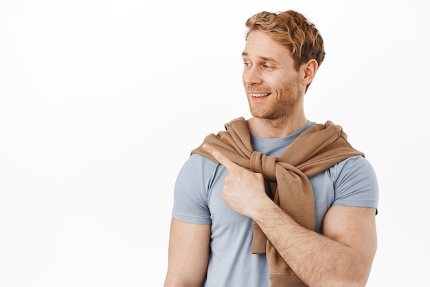 Smiling redhead man with muscles big biceps, pointing at upper left corner, showing advertisement on product on copy space, standing over white wall