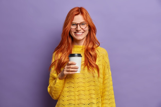 Smiling redhead millennial woman holds cup of coffee and has good mood enjoys lunch break expresses positive emotions visits best cafe takeaway wears casual clothes.