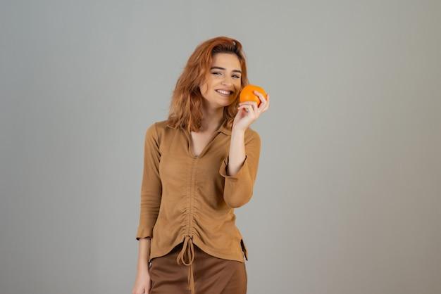 Smiling redhead sniffing fresh orange fruit on grey.