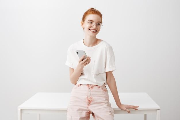 携帯電話を使用してテーブルに寄りかかって笑顔の赤毛の女性