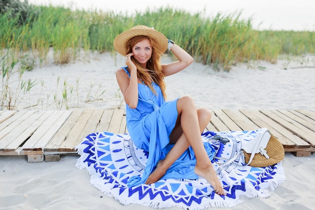 Smiling   redhead woman sitting on  beach towel .perfect tan body. blue dress. windy hairs.