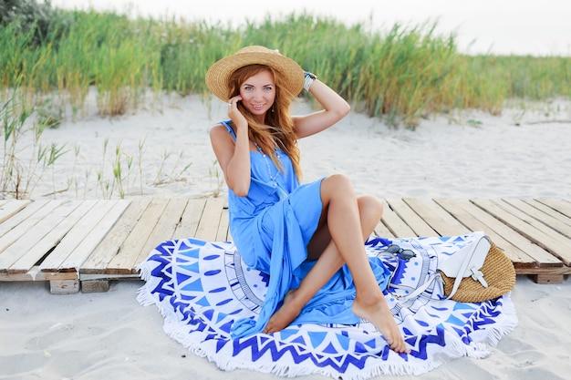 Улыбающаяся рыжая женщина, сидящая на пляжном полотенце. идеальное тело загара. голубое платье. волосы ветреные.
