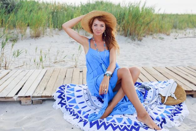 ビーチタオルの上に座って笑顔の赤毛の女性。完璧な日焼けボディ。青い服。風の強い髪。