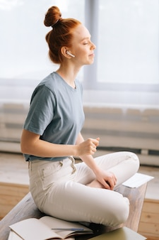 책상에 앉아 무선 이어폰으로 음악을 듣고 웃는 빨간 머리 젊은 여자