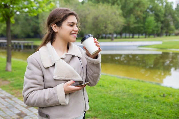 Smiling relaxed girl with phone drinking tasty coffee