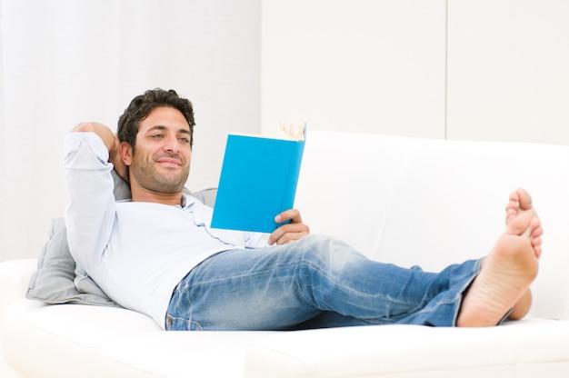 ソファーで横になっている本を読んでリラックスした男の笑顔