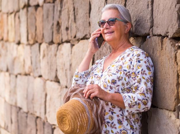 선글라스를 끼고 돌담에 기대어 스마트폰을 들고 이야기하는 웃고 있는 편안한 노년 여성