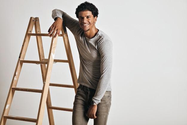 Modello giovane muscoloso alto e rilassato sorridente che indossa una maglietta a maniche lunghe grigio melange normale e jeans grigi sottili che si appoggia sulla scala a pioli di legno isolata su bianco.