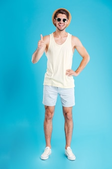 青い壁の上に立って親指を見せて帽子とサングラスでリラックスした若い男の笑顔
