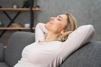 Smiling relaxed young woman leaning her head on sofa