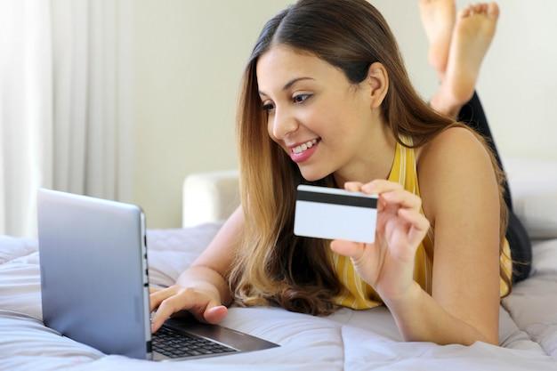 Улыбающаяся расслабленная молодая женщина, лежащая на кровати, вставляет номер кредитной карты в блокнот, делающий покупки онлайн дома
