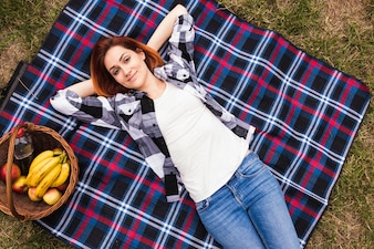 Smiling relaxed young woman lying on blanket at picnic