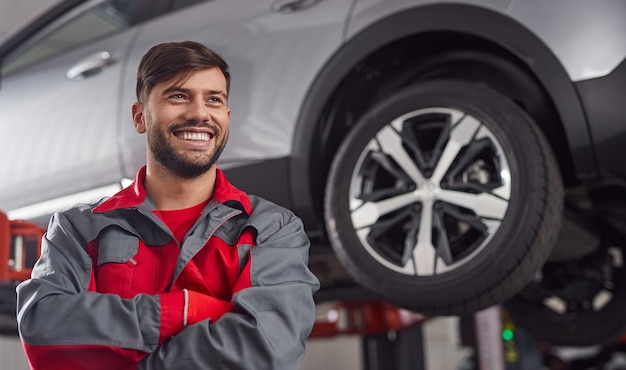 Smiling repairman sniling near suspended automobile in workshop