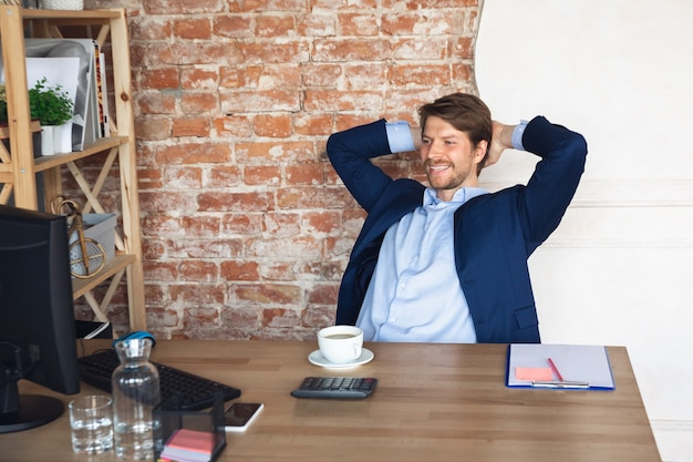 Smiling, resting, looks delighted, successful. young man, manager return to work in his office after quarantine, feels happy inspired. coming back to normal life. business, finance, emotions concept.