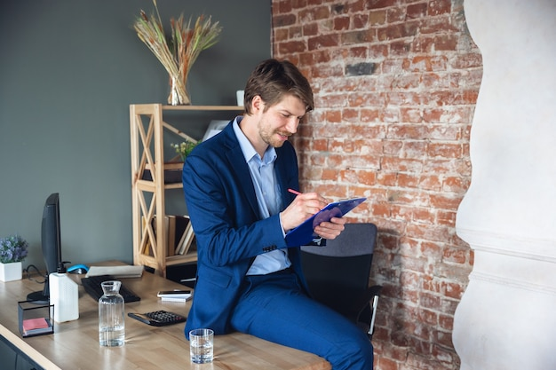 Smiling resting looks delighted successful young man manager return to work