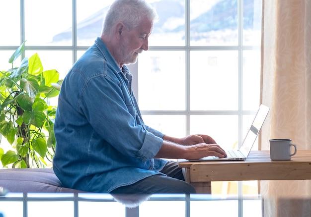 Улыбающийся пенсионер старший мужчина с бородой работает с ноутбуком дома. один современный пожилой человек, использующий беспроводные технологии