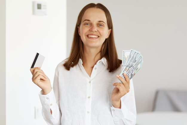 Smiling rich woman wearing white casual style shirt, winning lottery, holding credit card and dollar banknotes in hands, looking at camera with happy expression, posing in light room at home.