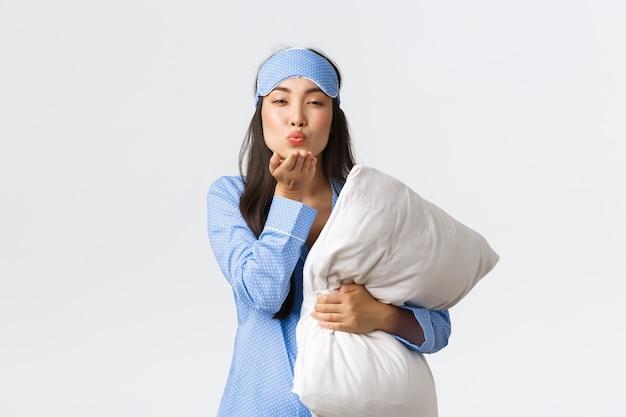青いパジャマとスリーピングマスクでロマンチックなアジアの女の子を笑顔、枕を抱き締め、コケティッシュで官能的な顔、白い背景に立っているカメラでおやすみエアキスを送信します。