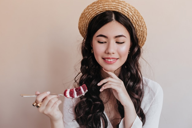 ケーキを食べるロマンチックなアジアの女性の笑顔。デザートを楽しむ上品な巻き毛の女性。