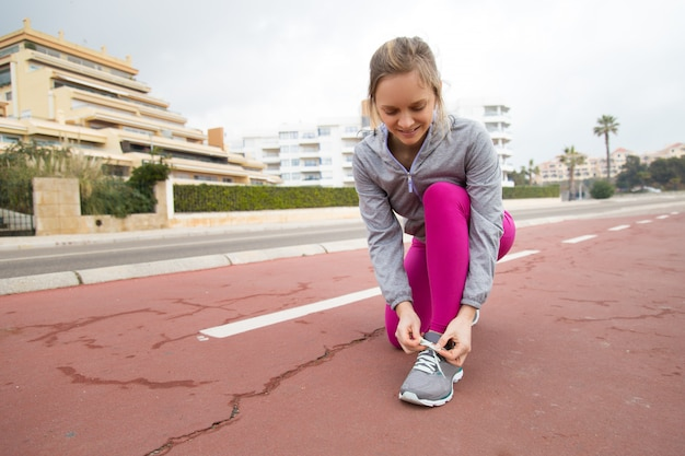 Smiling runner tying lace of sport shoe on stadium