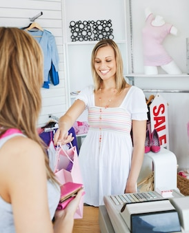 Smiling saleswoman giving clothes to a female customer