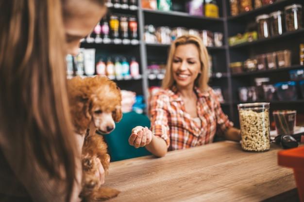 애완 동물 가게에서 일하는 웃는 판매원.