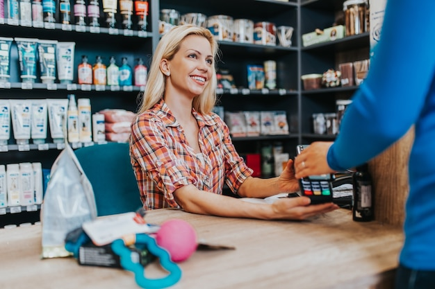 Smiling saleswoman working at pet shop checkout. electronic payment with card.
