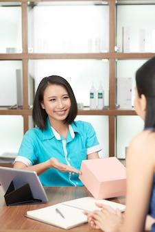 Улыбающийся администратор салона дарит подарок клиенту