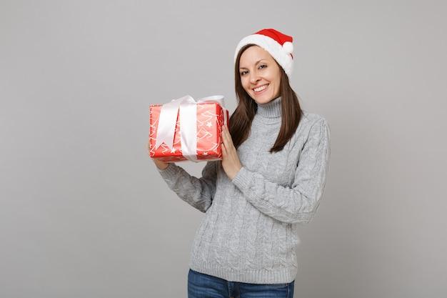 灰色のセーター、灰色の背景に分離されたギフトリボンと赤いプレゼントボックスを保持しているスカーフクリスマス帽子で笑顔のサンタの女の子。明けましておめでとうございます2019お祝いホリデーパーティーのコンセプト。コピースペースをモックアップします。