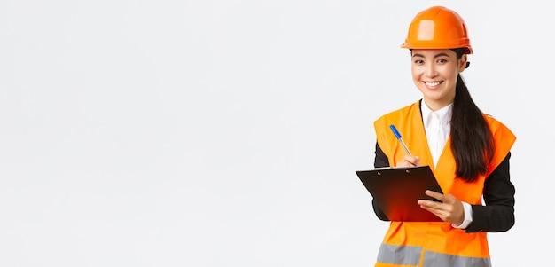 Улыбающаяся довольная азиатская женщина-строитель, ведущая инспекцию на предприятии, в защитном шлеме и светоотражающей куртке, записывает заметки и выглядит довольным результатом, белый фон