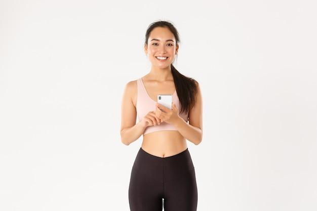 Улыбающаяся довольная азиатская фитнес-девушка, спортсменка, держащая смартфон, используя приложение для бега, проверяя сердечный ритм во время тренировки, белый фон.