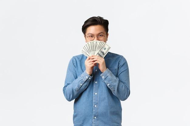 안경 쓴 만족한 아시아 남자가 돈 뒤에 얼굴을 숨기고 카메라 교활한 돈을 벌고 있는 모습을 보고 웃고 있습니다.