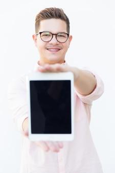 Smiling satisfied guy in eyeglasses showing blank tablet screen