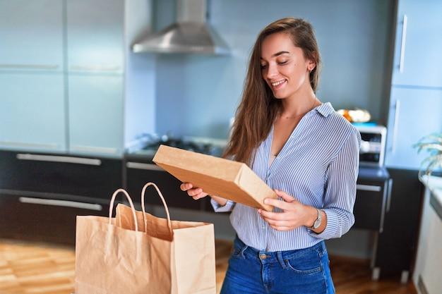 웃고 있는 행복한 캐주얼 성인 즐거운 젊은 밀레니엄 소녀 고객은 집에서 테이크아웃 음식과 음료가 포함된 판지 가방을 받았습니다. 빠른 배송 서비스 개념