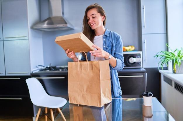 Улыбающаяся довольная, счастливая, повседневная взрослая, радостная молодая покупательница из поколения миллениума получила дома картонные пакеты с едой и напитками на вынос. концепция службы быстрой доставки
