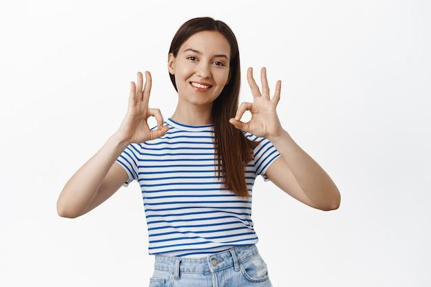 Улыбающаяся довольная, счастливая женщина показывает, что все в порядке, подписывает и кивает в знак одобрения, дает разрешение, хвалит и хвалит отличную вещь, стоя над белой стеной.