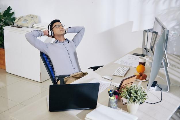 大きなプロジェクトの仕事を終えた後、彼の肘掛け椅子に寄りかかってヘッドフォンで満足しているインドのプログラマーの笑顔