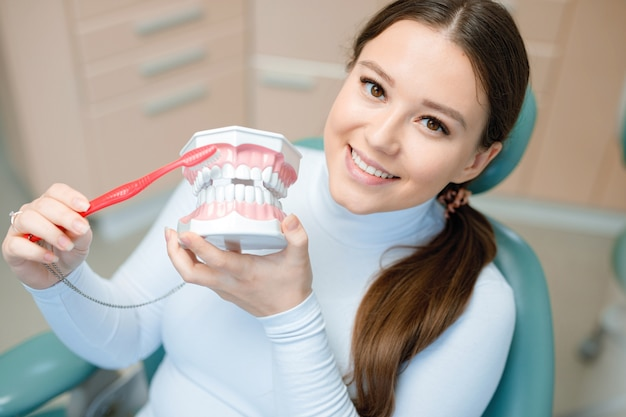 Smiling and satisfied patient at dentist's office after treatment.