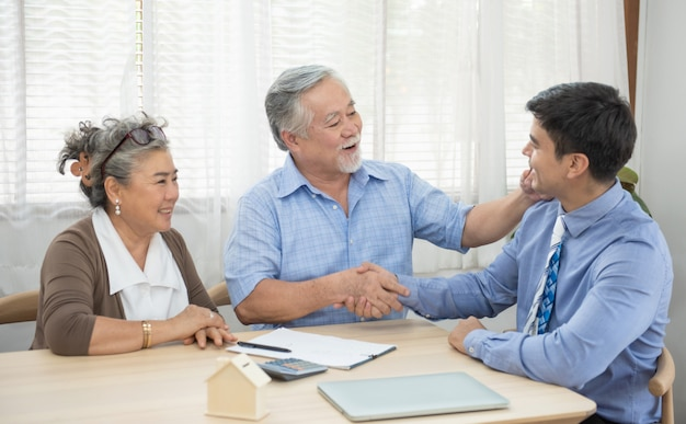 부동산 에이전트, 행복 한 노인 가족 및 브로커 악수 회의에서 새 집을 구입 동의 악수 판매 계약을 만드는 만족 된 수석 부부 미소.
