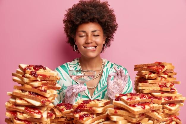 웃는 만족 한 여자가 입술을 물고 기쁨으로 눈을 감고, 괜찮은 제스처를 만들고, 칵테일을 마시고, 연회에 자유 시간을 보내고, 빵 샌드위치 더미 근처에 서고, 생일을 축하합니다.
