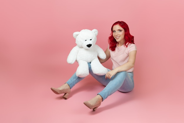 Smiling, satisfied woman in jeans with red hair with a large white teddy bear sitting on the floor
