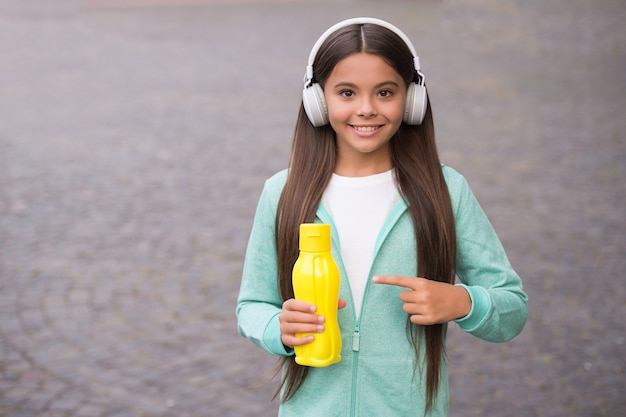 Smiling school girl in headset pointing finger on plastic bottle drinking water outdoor, copy space, thirsty.