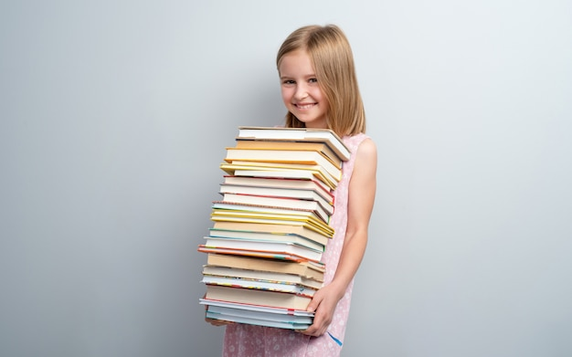 Smiling school girl holding stack of books isolated