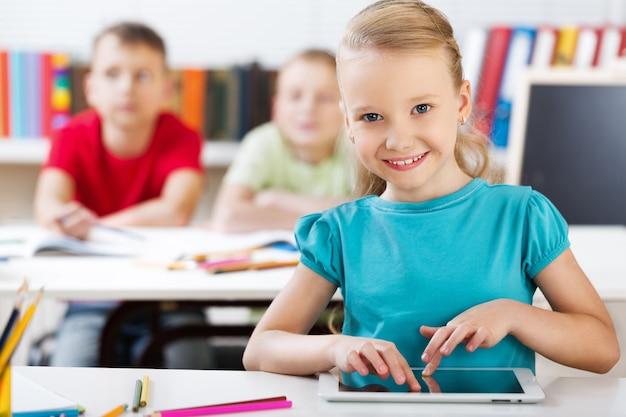 태블릿을 사용하여 교실에서 웃는 여고생